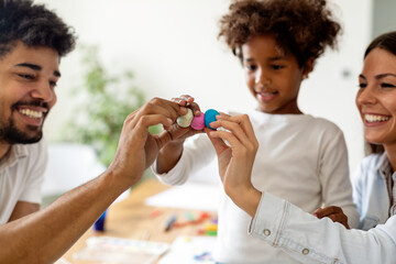 Happy multiethnic family spending time together at home. Parent child education fun concept