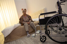 The Lonely Old Woman Sitting On The Bed With Wheel Chair