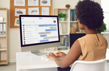 Black Business Lady Or Team Manager Sitting At Office Table, Looking At Web Page On Desktop Computer Monitor, Sending Messages To Private Or Collective Informal Work Chat. Online Communication Concept