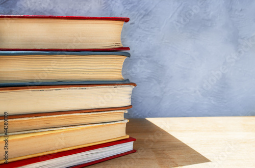 Stack of colorful hardback books on wooden table close up against gray and blue Fototapet