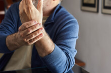 Close-up Of A Right Hand Holding The Wrist Of The Left Arm Of A Middle-aged White Man With Joint Pain.