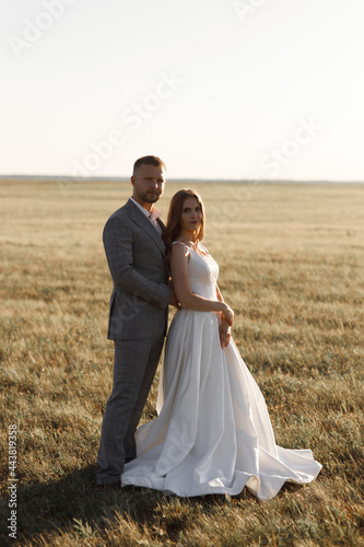 The bride and groom in the European style at sunset on the meadow Fototapet