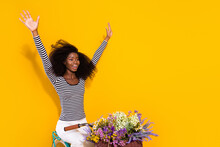 Photo Portrait Of Curly Woman Riding A Bike Enjoying Fresh Wind Keeping Hands Up Crazy Isolated Vivid Yellow Color Background