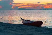 A Kayak With Oars Stands On The Shore Of A Sandy Tropical Beach Against The Backdrop Of A Colorful Sunset