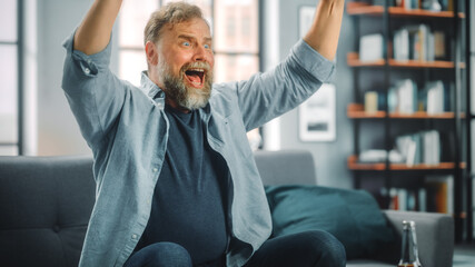 Charismatic Bearded Man Sitting on a Couch Watches Game on TV, Celebrates Sports when Team Wins Championship. Focused, Joyfully Intense and Authnetic Fan Cheers when Favourite Club Play