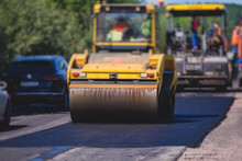Process Of Asphalting And Paving, Asphalt Paver Machine And Steam Road Roller During Road Construction And Repairing Works, Workers Working On The New Road Construction Site, Placing A Layer In Summer