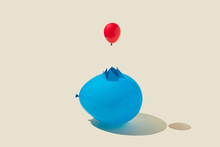 Small Red Party Balloon Comes Out Of A Cracked Large Blue One On Yellow Background. Minimal Abstract Concept. Isometric Layout. Rectangle With Copy Space.