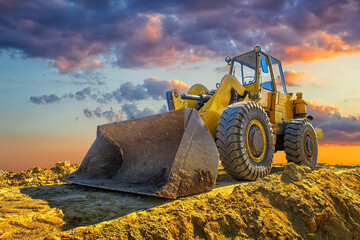 A stopping yellow excavator at a beautiful sunset