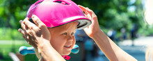 Close-up Mom Parent Hand Put On And Fasten Safety Helmet On Cute Blond Caucasian Toddler Girl For Riding Bike Or Scooter City Street Park Outdoors On Summer Day. Child Sport Activity Protection Care