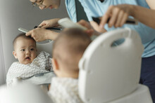 Portrait Of Asian Little Baby Boy Is Cutting Hair On High Seat By His Young Mother With Hair Clipper Together. Haircut At Home Concept