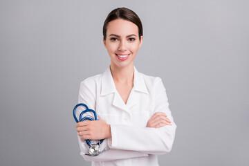 Photo portrait female doctor keeping sthethoscope smiling in white coat isolated grey color background