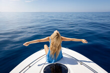 A Blonde Woman With Outstretched Arms Sits On A Boat Over Calm, Blue Sea And Enjoys Her Freedom
