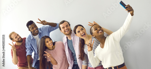 Foto Happy cheerful laughing young adult diverse college student friends doing V sign hand gesture taking group phone selfie picture in studio, enjoying best time of life, making memories together