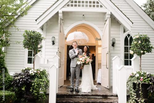 Billede på lærred bi racial bride and groom laughing in the rain outside church
