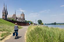 Woman Cycling Along River Meuse Near Dutch Village Cuijk