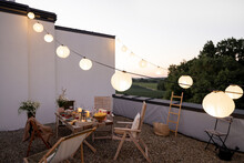 Beautifully Decorated Roof Terrace In Natural Boho Style With A Dining Table Full Of Food At Summer Time. Festive Dinner For A Small Group Of Friends At Dusk Outdoors