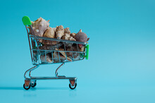 Holidays, Summer Travel Concept. Top View Of Supermarket Grocery Push Cart With Seashells In A Basket Close Up. Creative Concept Of Shopping. Economy Concept.