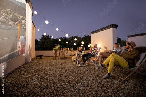 Small group of people watching movie on the rooftop terrace at sunset Fototapeta