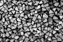 Textured Firewood Background Of Chopped Wood For Kindling And Heating The House. A Woodpile With Stacked Firewood. The Texture Of The Birch Tree. Toned In Black White Or Gray Color