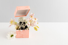 Decorative Gift Box With Flowers And Skull Against White And Gray Background. Creative Halloween Party Concept.