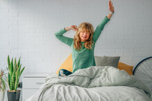 Woman Waking Up With Joy In The Room With Raised Arms Stretching