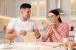 Leinwandbild Motiv Happy couple wearing pyjamas and cooking together in kitchen