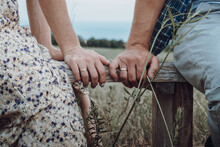 Portrait Photo Session Of Bride And Groom On The Field Of Village In Country Style. Light Tone Wedding On Nature Among Dry Grass. Man And Woman Are Wear Country Clothes Sitting On Bench Cute Talking.
