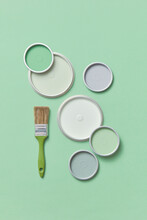 Different Lids Of Paints On Green Background