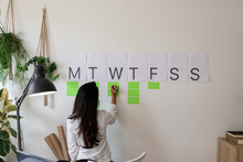 Writing Notes In A Weekly Wall Organizer