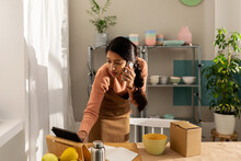 Woman Calling By Phone And Using Her Tablet At Workplace