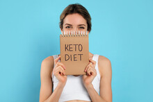 Woman Holding Notebook With Phrase Keto Diet On Light Blue Background