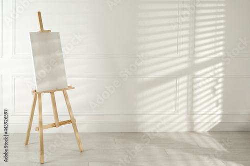 Canvas Print Wooden easel with blank canvas near light wall. Space for text