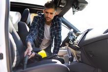 Man Vacuuming The Interior Of A Car