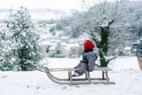 baby girl on a sled in the snow