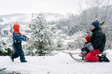 baby girl  and young woman on sled, pulled by toddler sister