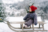baby girl on a sled on a snowy day