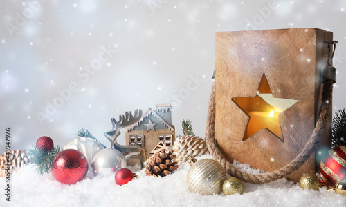 Composition with wooden Christmas lantern on snow against light grey background