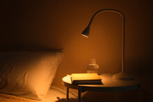 Glowing Lamp And Book On Table In Dark Bedroom