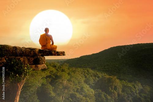Fotografie, Tablou Buddhist monk in meditation at beautiful sunset or sunrise background on high mo