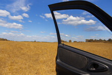 View Of The Yellow Field And The Blue Sky With Clouds From The Open Car Door.