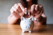Closeup Image Of A Woman Putting Coins Into Piggy Bank For Saving Money Concept