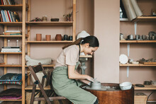 Young Woman Pottery Maker Works In Clay Studio On Pottery Wheel Against Shelves With Vases And Pots. Creative People Concept, Small Business.
