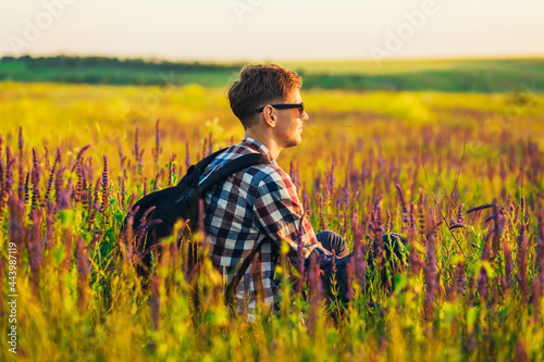Fotografia Young man in sunglasses sitting in a field with wildflowers, man in the countrys
