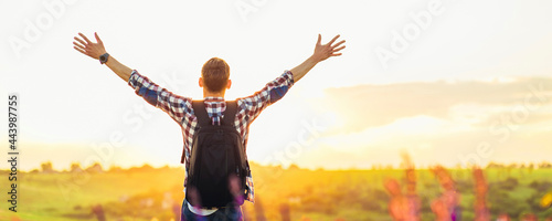 Fotografia Traveler with raised hands standing on a hill in green grass and enjoying a maje