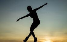 Graceful Ballerina. Sensual Woman Silhouette On Sky Background. Sensuality
