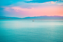 Bright Beautiful Sunrise At Sea. A Scenic View Of A Colorful Sky Above The Ocean. Orange And Blue Clouds. Beautiful Landscape Of A Ocean Bay. Scenic View Of Mountains And Sea. Colorful Sunrise Sky