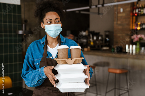 Fototapeta Black waitress in apron holding food boxes while working at cafe