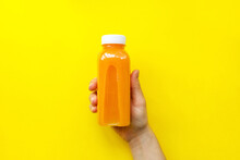 Female Hand Holding Plastic Bottles With Orange Juice Or Smoothie On Yellow Background. The Concept Of Diets, Detox. Bright Background, Flat Lay, Top View