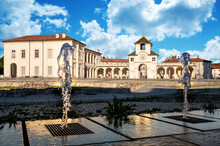 Venaria Reale,Piedmont,Italy. June 2021. Stunning View Of The Clock Tower Which Is The Entrance To The Palace. On A Beautiful Sunny Day With Blue Skies And White Clouds, The Jets Of The Fountain Frame