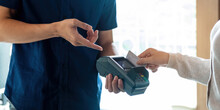 Close Up Of Hand Of Customer Paying With Contactless Credit Card